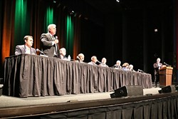 FIRED UP:  Cal Poly hosted the first major debate among candidates vying for the vacant seat representing California's 24th Congressional District. Candidates, from left to right: Justin Fareed, William Ostrander (standing), John Uebersax, Katcho Achadjian, Salud Carbajal, Steve Isakson, Matt Kokkonen, Helene Schneider, and Jeff Oshins. KCBX-FM News Director Randol White, far right, moderated the event. - PHOTO BY DYLAN HONEA-BAUMANN