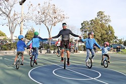 "ALL TOGETHER NOW:  VonJon and handful of young unicycle enthusiasts link arms and pedal clockwise in unison at Meadow Park in San Luis Obispo. Led by Mark Wilder, the SLO Juggling and Unicycling Club has been gathering at the park to practice and learn for about five years. Wilder tries to provide individual coaching to each kid who comes on Tuesdays. ""That's what keeps them coming back,"" he said. - PHOTO BY DYLAN HONEA-BAUMANN"