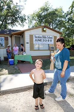 NUTRITION:  A mother, Cheryl, and her 4-year-old son, Zaden, pick up dinner at the People's Kitchen in Paso Robles before walking across the street to Pioneer Park. - PHOTOS BY DYLAN HONEA-BAUMANN