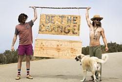 LEAVE NOTHING BUT MEMORIES:  Nate Ross (left) and Logan Leggs (right), of Nomadic Artifacts, hold up a sign made from bottle caps that they collected at Pirate's Cove. - PHOTO COURTESY OF VAGABOND INK.