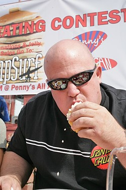 """THE CHAMP!:  Daniel """"Doughboy"""" Arndt put away 7 3/4 plate-size pancakes in four minutes to win the seventh annual Pancake Eating Contest at Penny's All American Café to benefit AmpSurf. - PHOTO BY GLEN STARKEY"""