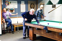 OUT AND ABOUT:  Regulars at the 100-year-old pool table in the Morro Bay Senior Center are left to right: Wayne Gillmore, 79, Peter Gabriel, 66, and Rey Hudson, 85. They play pool for about three hours every day. Centers like this one help provide opportunities for SLO County seniors to stay active and engaged in their community. - PHOTO BY JAYSON MELLOM