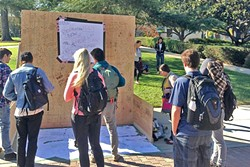 """MEAN SCRIBBLES:  Cal Poly students gather around a """"free speech wall"""" erect by the Cal Poly College Republicans last November. Anonymous students wrote bigoted messages about the religion of Islam and transgender students. The incident jumpstarted a student social movement: SLO Solidarity. - FILE PHOTO BY PETER JOHNSON"""