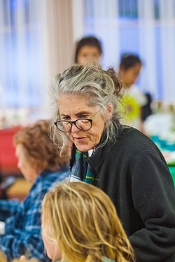 ONE ON ONE:  Sharon O'Leary, director for the Community Resource Connections office in Morro Bay, takes time at a community dinner to chat with people who might need help connecting to services. - PHOTO BY JAYSON MELLOM
