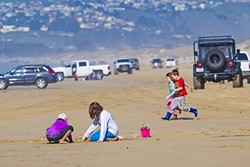 SAND, SUN, VEHICLES:  Children play on the strip of beach between Pier Avenue and Arroyo Grande Creek, the sandy road that takes drivers to the 1,500 acres of Oceano Dunes that are available for off-road recreation and camping. - PHOTO BY JAYSON MELLOM