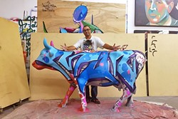 A COW OF A DIFFERENT COLOR:  Artist Man One stands with a cow he painted for the public art show, COWABUNGA, in Dana Point, Calif. Man One will paint another cow live for the Cow Parade in SLO on Sept. 17. - PHOTO COURTESY OF MAN ONE