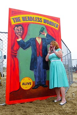 PRETTY AS A CARNIVAL PICTURE:  Anna Starkey got all dolled up in '40s garb, posing here with one of the many props scattered along the beach raceway. - PHOTO BY GLEN STARKEY