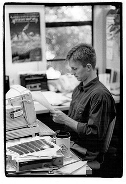 WORKING HARD?:  A young Steven T. Jones looks over a document at his 'New Times' desk. - FILE PHOTO
