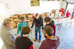 COME TOGETHER:  Volunteers for the Catholic Worker pray together before handing out groceries to whoever needs them at the group's weekly food bank. - PHOTO BY JAYSON MELLOM