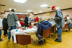 CHRISTMAS CHEER:  Morro Bay City Council members Robert Davis (right) and Marlys McPherson (center) give out hats and cookies to attendees at a community dinner in Morro Bay the week of Christmas. - PHOTO BY JAYSON MELLOM