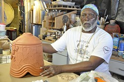STACK IT UP :  Alonzo Allen Jr. talks about how he creates his ceramic pieces, such as this bell that is waiting for spots of color and glaze. - PHOTO BY CAMILLIA LANHAM