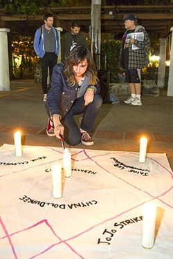 VICTIMS OF VIOLENCE:  Robin Foss of The Queer Crowd SLO lights candles in Mission Plaza on March 2 for a vigil in memory of six transgender women killed in the U.S. in the first two months of 2017. - PHOTO BY JAYSON MELLOM