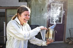 "CAN WE BEE FRIENDS?:  A smoker subdues the bees as Lindsey Morgan pulls frames from her single hive located in her Morro Bay backyard. The amateur beekeeper swears the colony mysteriously ""found her."" - PHOTO BY JAYSON MELLOM"