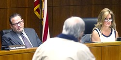 BOARD DIVIDED:  SLO County Supervisors Adam Hill (left) and Lynn Compton (right) listen to public speakers at a recent Board of Supervisors meeting. Hill and Compton landed on opposite sides of a heated groundwater policy debate and whether to welcome an investigation into alleged Brown Act violations committed by board members. - PHOTO BY JAYSON MELLOM