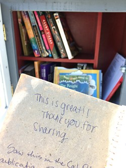 COMMENTS Some little libraries have comment books where borrowers can write about their experience of stumbling upon the little box on a walk around the neighborhood. - PHOTO BY KAREN GARCIA