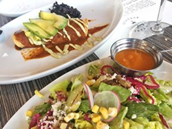 PLANT PARTY The Vegetable Butcher's market enchilada filled with kale and black beans topped with cashew crema and avocado is paired with the Little Casa salad, with little gem, raddicchio, avocado, radish, hibiscus pickled onion, queso fresco, sweet dried corn, bourbon pepitas, and cilantro vinaigrette. - PHOTO BY REID CAIN
