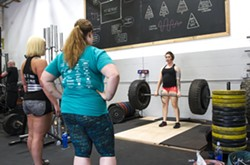 PUSHING YOURSELF At 31 weeks pregnant in June, Brandy French, far right, still takes part in SLO Strong workouts, pictured here lifting 225 pounds. - PHOTO BY JAYSON MELLOM