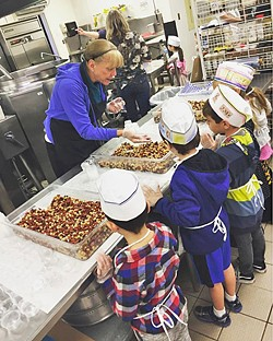 LINING UP San Luis Coastal Unified School District food service worker Jane Nichols demonstrates to first graders how to cup beans for the salad bars at the district's central kitchen. - PHOTO COURTESY OF ERIN PRIMER