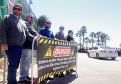 IN THE STREETS Members of IBEW Local 639 hold a banner at the construction site of a Pismo Beach hotel to protest the use of uncertified electricians. - PHOTO BY CHRIS MCGUINNESS