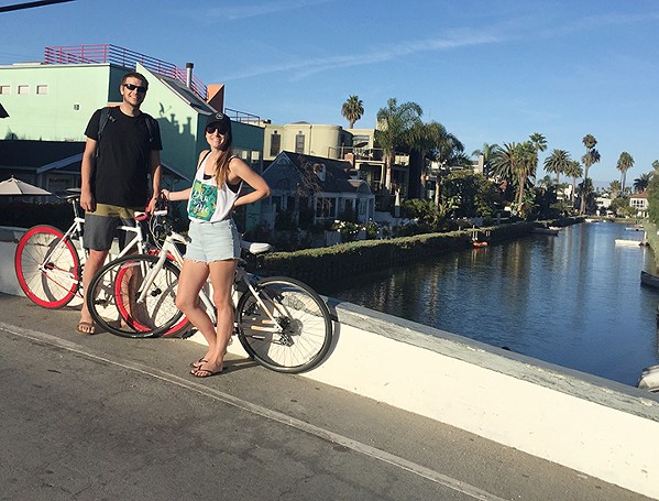BRO AND SIS My sister, Lisa, and I stop our bikes for a quick photo next to the Venice canals. - PHOTO COURTESY OF JOHN STEIN