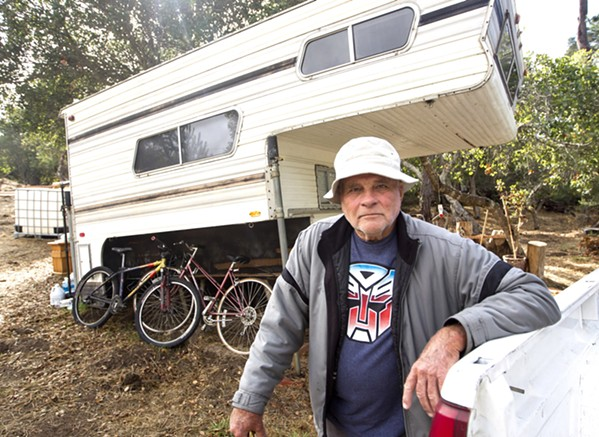 HOME William Carlyle, 76, stands in front of a trailer on his vacant lot in Cambria. He lost his home in the Santa Margarita Hill Fire last June, and he now faces penalties from SLO County for code violations. - PHOTO BY JAYSON MELLOM