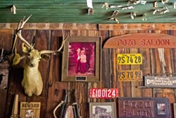 DOLLAR BILLS AND BULLET HOLES? Dozens of dollar bills have been pinned to the saloon ceiling by patrons, and some speculate that Wild West-era bullets left holes up there. - PHOTO BY JAYSON MELLOM