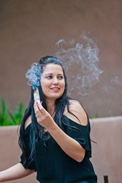WITCHY WOMAN Shelby Bundy, owner of Tamed Wild Apothecary in Arroyo Grande, demonstrates how to sage and purify oneself during a full moon ritual. - PHOTO BY JAYSON MELLOM