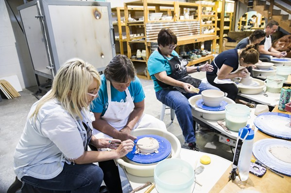 LEARN Susan Bass, owner of Pottery Coast in Grover Beach, teaches a student how to properly use the potter's wheel during a class. - PHOTO BY JAYSON MELLOM