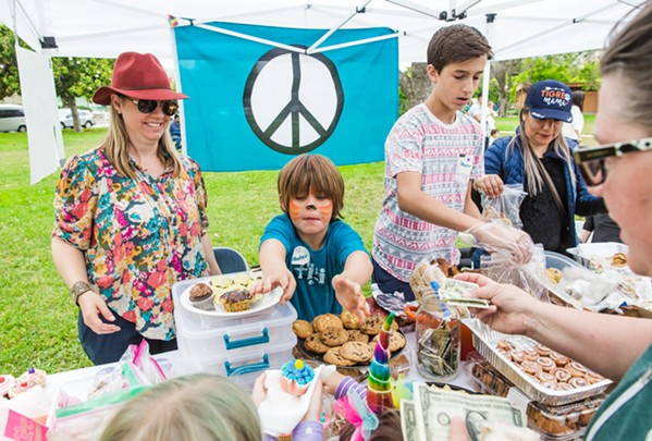 BAKE FOR A CAUSE Ryder Heenan (center), 6, his mother Kristen Heenan (left), and Nathan Durant (right), 14, sell homemade goodies in the Kids for Kids event on June 24 in Mitchell Park. The bake sale raised more than $3,300 for immigrant families who have been separated at the U.S. border. - PHOTO BY JAYSON MELLOM