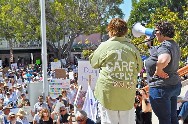 READY TO RALLY Gina Whitaker (left) and Alex Lancaster address a 1,500-strong crowd in front of the SLO County courthouse at a June 30 protest against the separation of undocumented immigrant children from their families by the Trump administration. - PHOTO BY ASHLEY LADIN