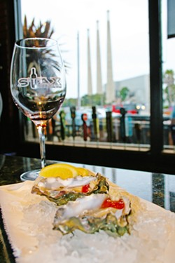 ON THE HALF SHELL Oysters on the half shell, local wine, and a beachy view? This is real life at Stax Wine Bar in Morro Bay. Owned by Giovanni DeGarimore of Giovanni's Fish Market & Galley, Stax is able to offer up fresh seafood whenever a good catch is hauled in from the bay. - PHOTO COURTESY OF REID CAIN
