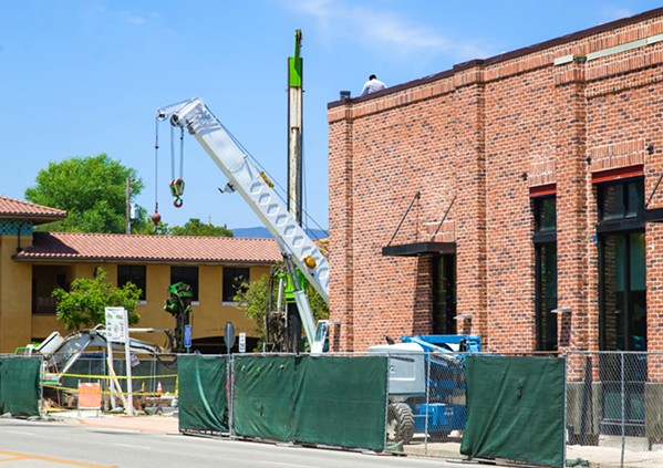 UNDER DEVELOPMENT Cranes, such as this one at a project on Santa Rosa Street, have been visible at sites all over San Luis Obispo, pointing to an economic upswing and commercial/residential development. - PHOTO BY JAYSON MELLOM