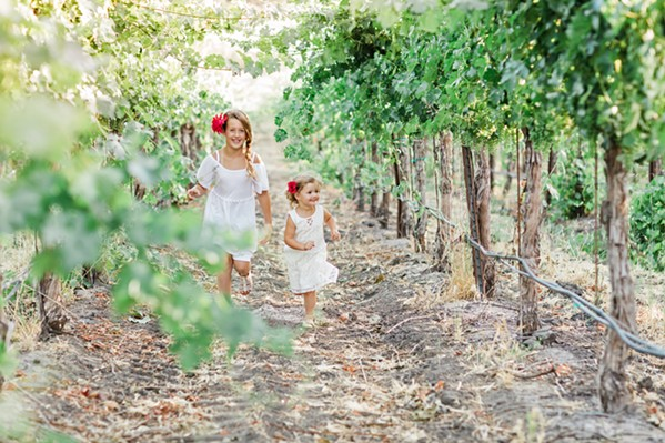 """SHOOT FOR THE STARS Macoy Sill and Cecilia Higgins frolic in the vines. When little girls are asked what they want to be when they grow up, Dream Big Darling founder and CEO Amanda Wittstrom-Higgins wants careers like """"vineyard manager"""" and """"wine sales rep"""" to spring to mind. - PHOTO COURTESY OF DREAM BIG DARLING"""