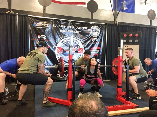 ON HER SHOULDERS Denise Juarez (97 pounds) goes down for a squat at a competition in Santa Clarita in 2017. Today she holds the world record in the squat for her age and weight class: 231.5 pounds. - PHOTO COURTESY OF DENISE JUAREZ