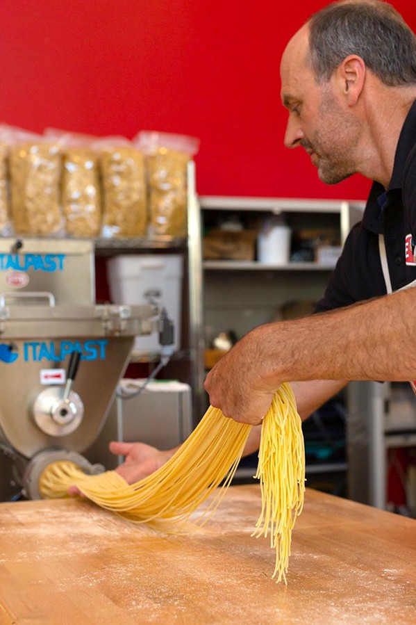 FLOUR ON HIS HANDS Lloyd Herrera guides freshly made linguine through a state-of-the art imported Italian pasta machine at Etto in Paso Robles' Tin City. - PHOTO COURTESY OF LEILA SAPPA