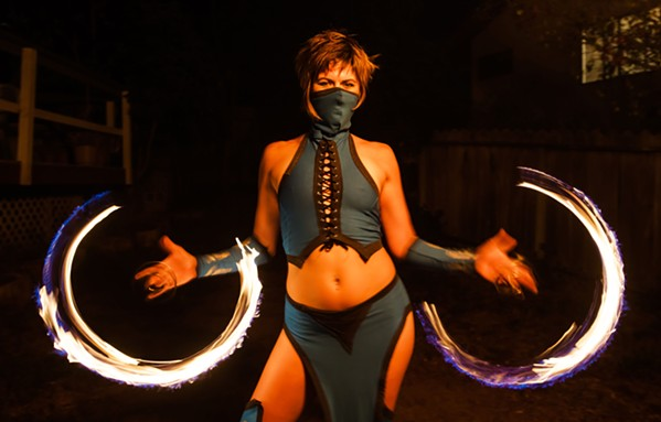 RINGS OF LIGHT Flow artist Gwendolyn Hodgson from Ignite Fire Dance spins poi rings around her fingers. - PHOTO BY JAYSON MELLOM