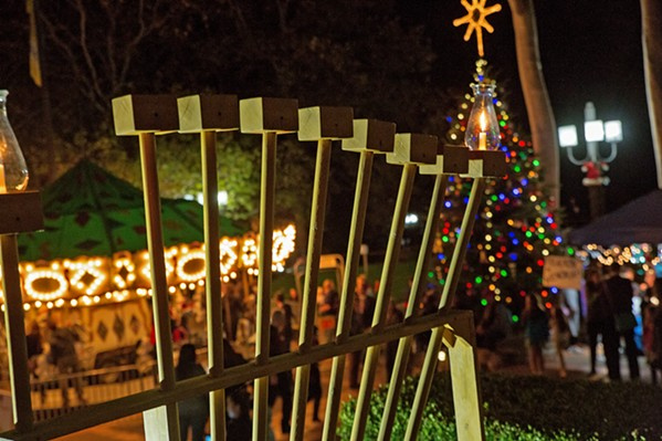 EIGHT NIGHTS OF OIL The first candle on the menorah shines bright in SLO's Mission Plaza in December 2017 on the first night of Hanukkah. - PHOTOS COURTESY OF THE JCC OF SLO