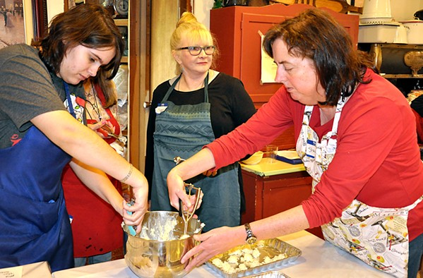 COCONUTS Sheree Garcia (left) and Stacey Bassett (right) scoop coconut and white chocolate into round balls as Jasmyn Carpenter checks out the turtle bark demo happening at the next table over. - PHOTOS BY CAMILLIA LANHAM