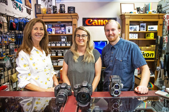 SERVICE AND A SMILE Swing into The Photo Shop for a tactile shopping experience (Get off the internet, people!) with Peggy Mesler (owner), Annie Wald, and Joseph Ardnt (left to right), who can answer your questions in person, can walk you through the ins and outs of camera equipment right then and there, and might even flash you a grin every now and then. - PHOTO BY JAYSON MELLOM