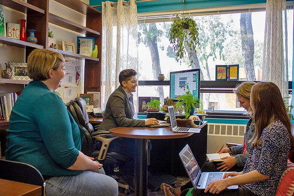 EXPANDING SERVICES Dr. Jay Bettergarcia, a Cal Poly psychology professor (at desk), leads the SLO ACCEPTance Project, a four-year venture that delivers 9-month trainings to local therapists to strengthen their competency with LGBTQ clients. - PHOTO COURTESY OF CAL POLY