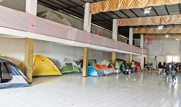 """WAITING GAME In Tijuana, Mexico, there's a small church nicknamed """"Little Haiti"""" where displaced Haitian immigrants take shelter. - PHOTO COURTESY OF BILL STRUTER"""
