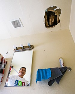 UNCOMFORTABLE In one unit of the Grand View Apartments in Paso Robles, a gaping hole above the bathroom sink often spills debris. - PHOTOS BY JAYSON MELLOM