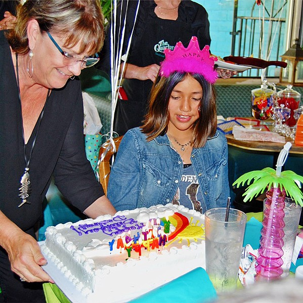 WRAPPED UP HAPPINESS Jeff Edwards celebrated Destiny's (right) 10th birthday, and Quarterdeck Seafood Restaurant owner Cyndy Jones (left) was among the guests. - PHOTO COURTESY OF CANDLES FOR KIDS
