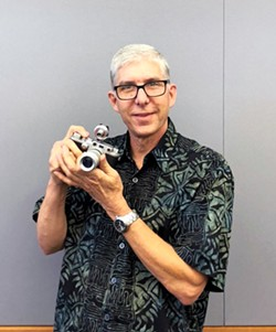 THE MAN BEHIND THE CAMERA Steve Udell poses with one of the cameras he used for his photos in the exhibit at Atascadero Library. - PHOTO BY MALEA MARTIN