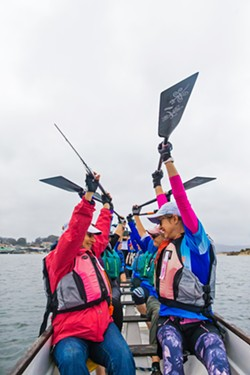 CAMARADERIE Paddlers celebrate after completing a dragon boat practice race in Morro Bay on Sept. 28. - PHOTO BY JAYSON MELLOM