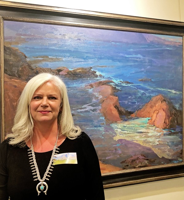 CONTEMPORARY GREATS Lori Putnam stands with her work titled Harmony Headlands. Her inspiration, Edgar Payne's Dana Point, is hung right next to Putnam's modern take. - PHOTO BY MALEA MARTIN