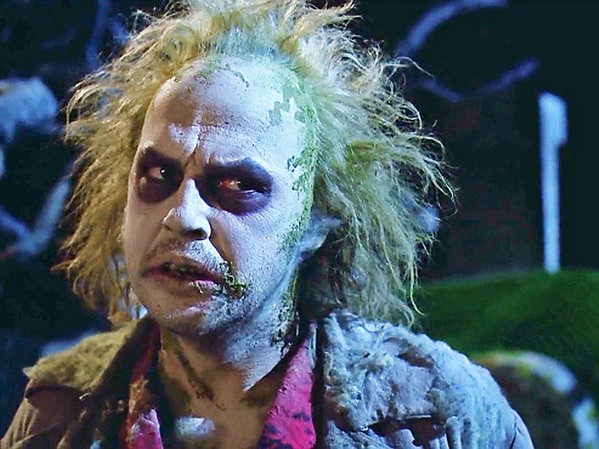 SAY IT THRICE Michael Keaton stars as Betelgeuse, a malicious spirit hired by a recently deceased couple to help them drive an obnoxious family out of their house, in the 1988 Tim Burton horror-comedy classic, Beetlejuice, screening on Oct. 20, in Galaxy Colony Square 10 Theaters. - PHOTO COURTESY OF THE GEFFEN COMPANY