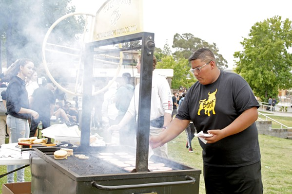 SCHOOL BARBECUE SLO High School Associated Student Body members throw patties on a grill at the school's first Student of the Month Barbecue of the year on Sept. 27. - PHOTO BY KASEY BUBNASH