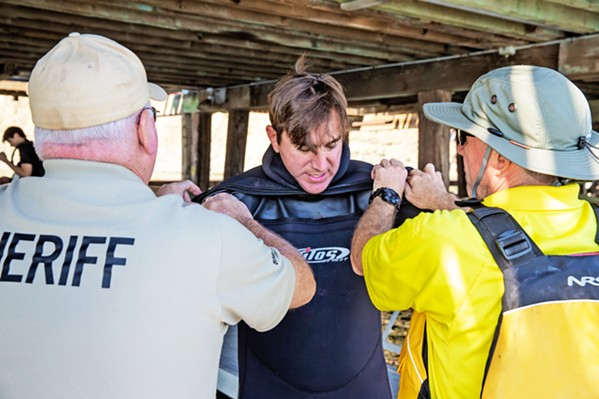 GETTING READY SLO Sheriff's Deputy and dive team member Matthew Shields gets wetsuit help from teammates Pat Nugent (right) and JD Cronin at an Oct. 12 training at Port San Luis. - PHOTO BY JAYSON MELLOM