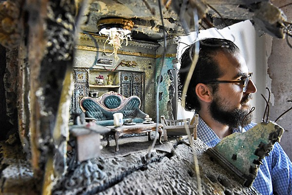 AN ARTIST AND HIS WORK Artist Mohamad Hafez is seen through one of his sculptures, which features mini-house scenes situated among found objects. - PHOTO COURTESY OF MOHAMAD HAFEZ